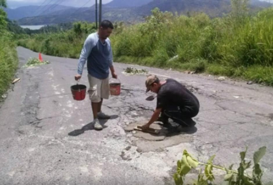 Un grupo de vecinos de Amatitlán tomó la iniciativa de reparar los baches de la antigua carretera hacia ese municipio. (Foto: Pampichi News)