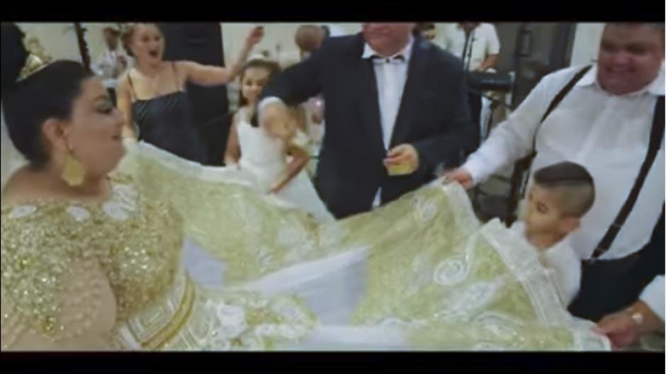 Durante la fiesta, los invitados levantaron el vestido de la novia para bailar al su alrededor. (Captura Youtube)