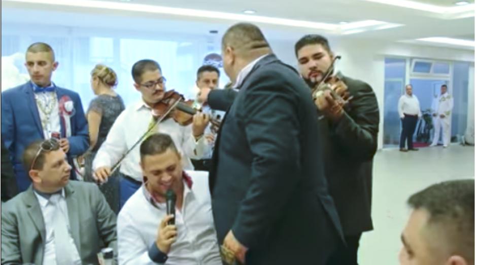 El padre de la novia repartía dinero a cada uno de los músicos que participaron en un encuentro previo a la ceremonia religiosa. (Captura Youtube)