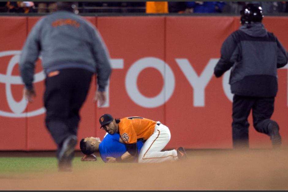 Ángel Pagán sostiene al aficionado contra el suelo. (Foto: John Soohoo/Dodgers)