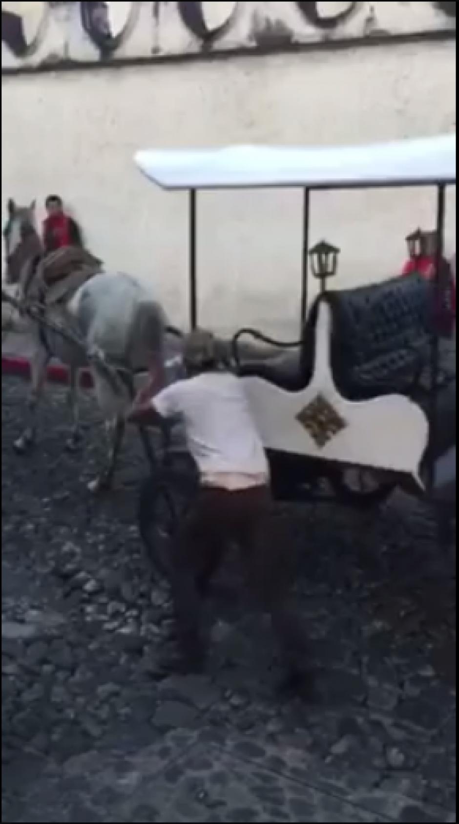 Apoyado por un jovencito, el carruaje es llevado a un lugar donde no estorbe. (Captura Facebook)