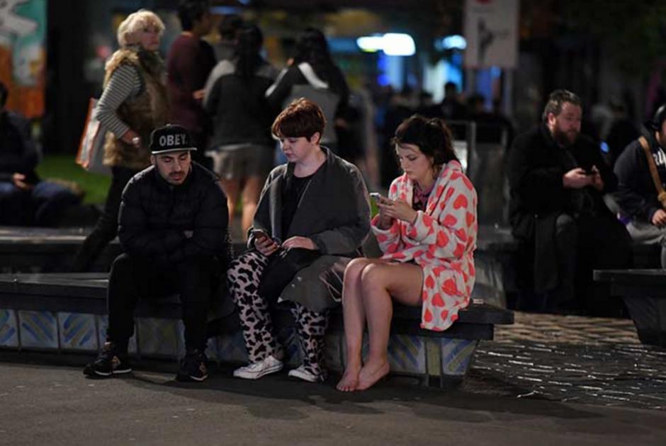 Varias personas esperan en las afueras de sus casas. (Foto: AFP)