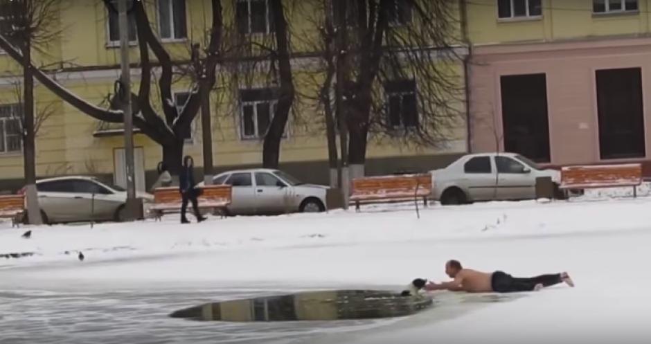 A este hombre no le importó quitarse la camisa y tirarse sobre el hielo para salvar un perro atrapado entre aguas congeladas. (Foto: Captura de video)
