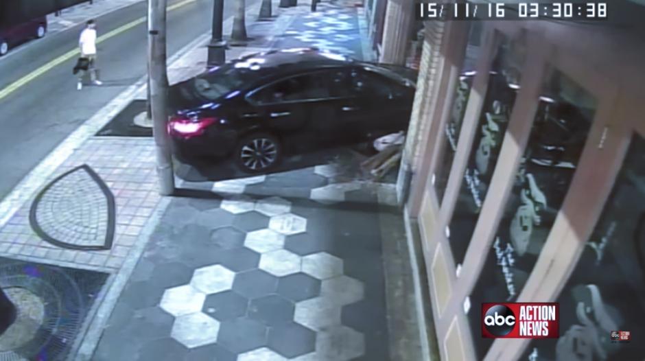 El carro rompe la pared de un bar con todo y uno de los revoltosos. (Imagen: captura de YouTube)