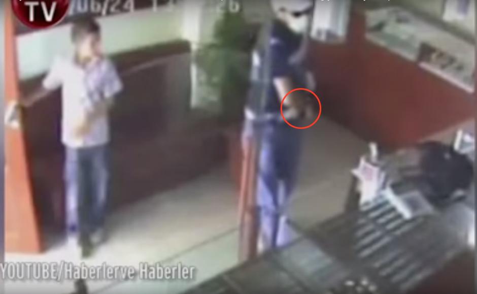 Al momento de entrar, deja un maletín en el mostrador y saca su arma. (Imagen: captura de YouTube)