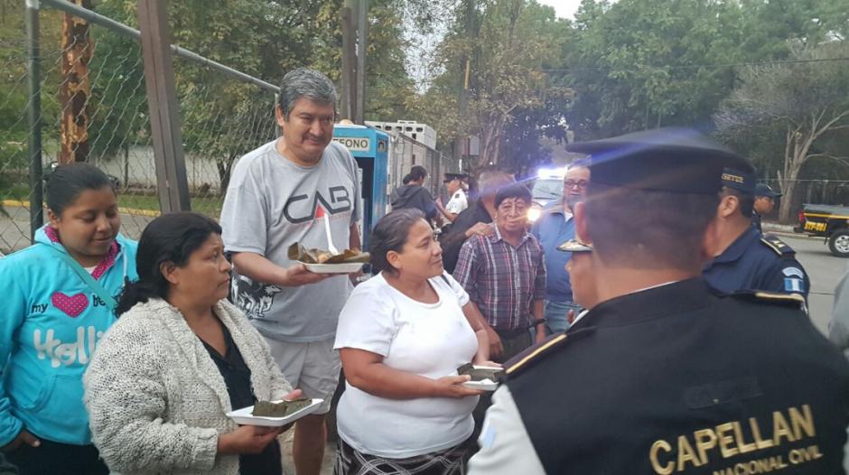 Varias mujeres que se encontraban afuera de los hospitales recibieron la comida. (Foto: PNC)