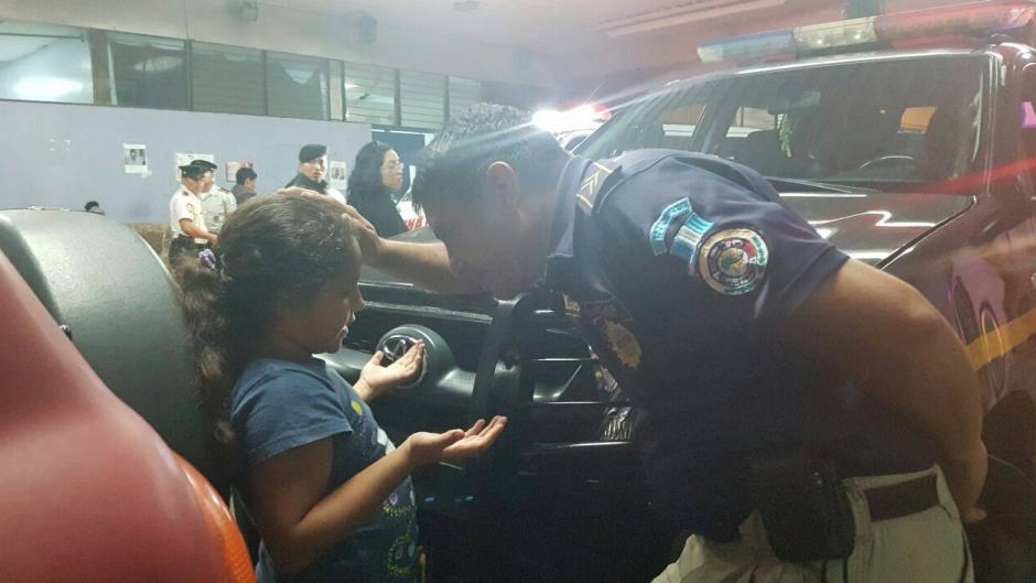 El agente de la PNC realiza una oración con la niña. (Foto: PNC)