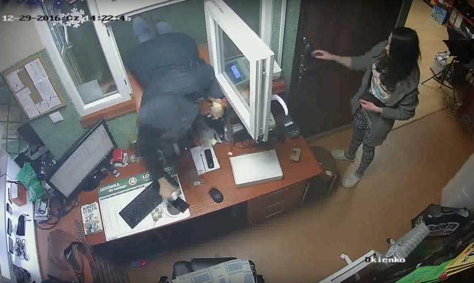 Mientras la empleada asegura la puerta, la asaltante introduce parte de su cuerpo por la ventanilla. (Imagen: captura de YouTube)