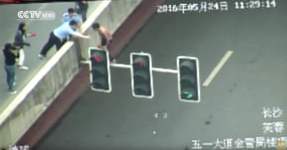 Un hombre intenta tirarse desde un semáforo. (Captura de pantalla: CCTV News)