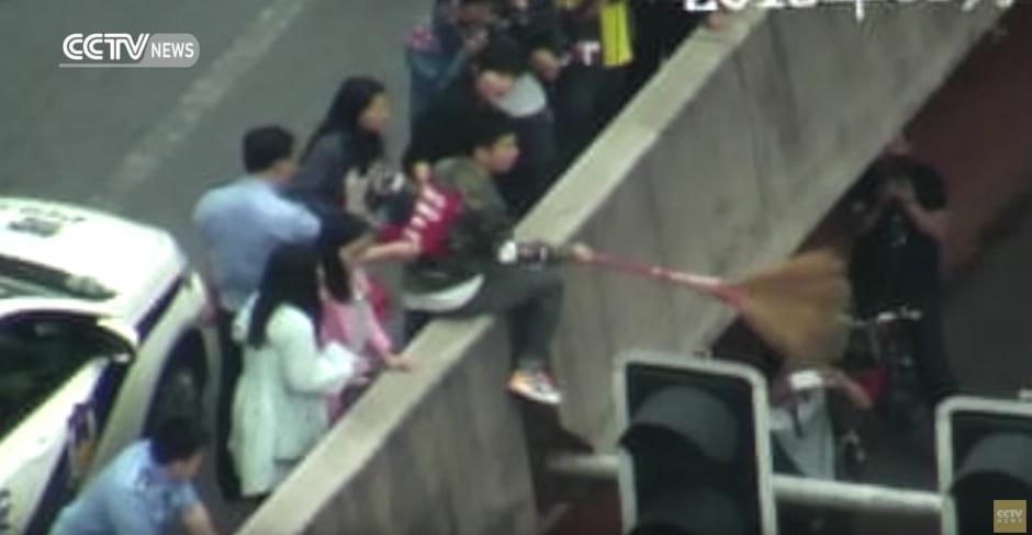 Un hombre intenta ayudar con una escoba. (Captura de pantalla: CCTV News)