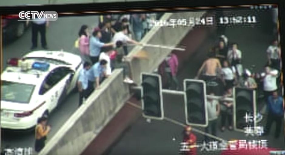 El hombre mira el tubo y no se agarra. (Captura de pantalla: CCTV News)