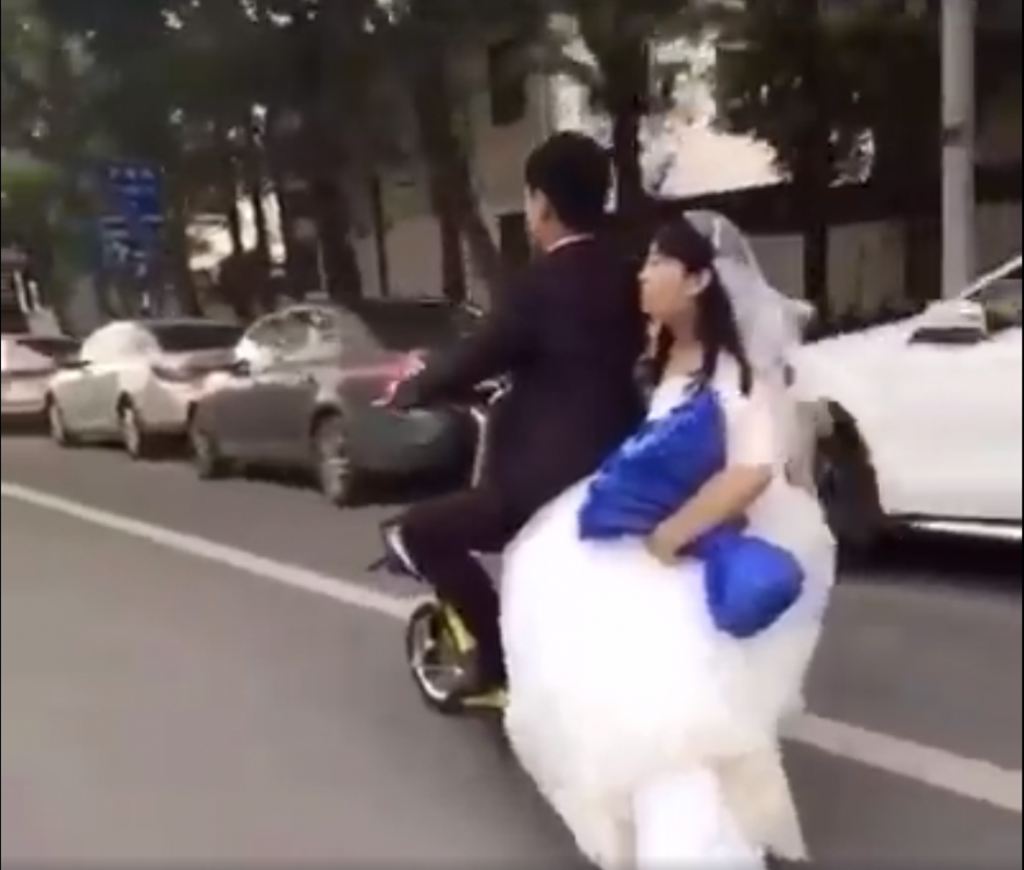 La pareja de recién casados circula por las calles de China. (Captura de pantalla: People's Daily, China/Facebook)