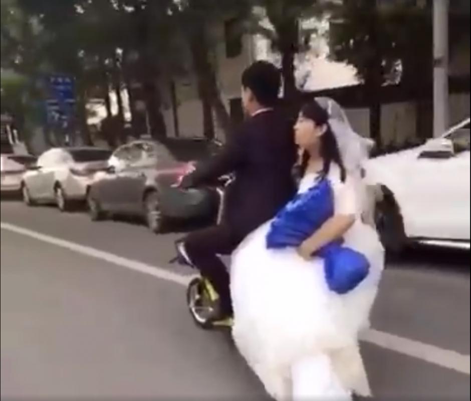 La pareja de recién casados circula por las calles de China. (Captura de pantalla: People's Daily, China/Facebook)