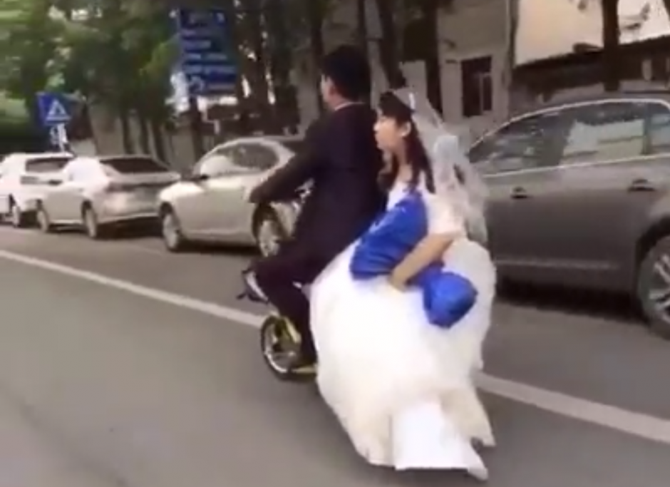 Los novias van en una motocicleta. (Captura de pantalla: People's Daily, China/Facebook)