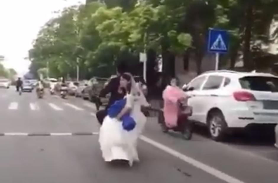 La joven luce un enorme ramo de flores y un hermoso vestido blanco. (Captura de pantalla: People's Daily, China/Facebook)