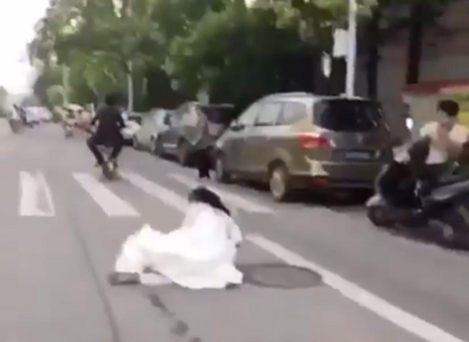 La novia se cae del vehículo. (Captura de pantalla: People's Daily, China/Facebook)