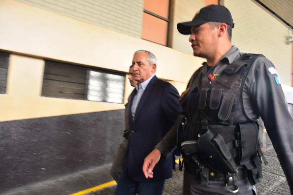 El exmandatario Pérez Molina es acompañado por un guardia de seguridad en su ingreso a Tribunales. (Foto: Jesús Alfonso/Soy502)