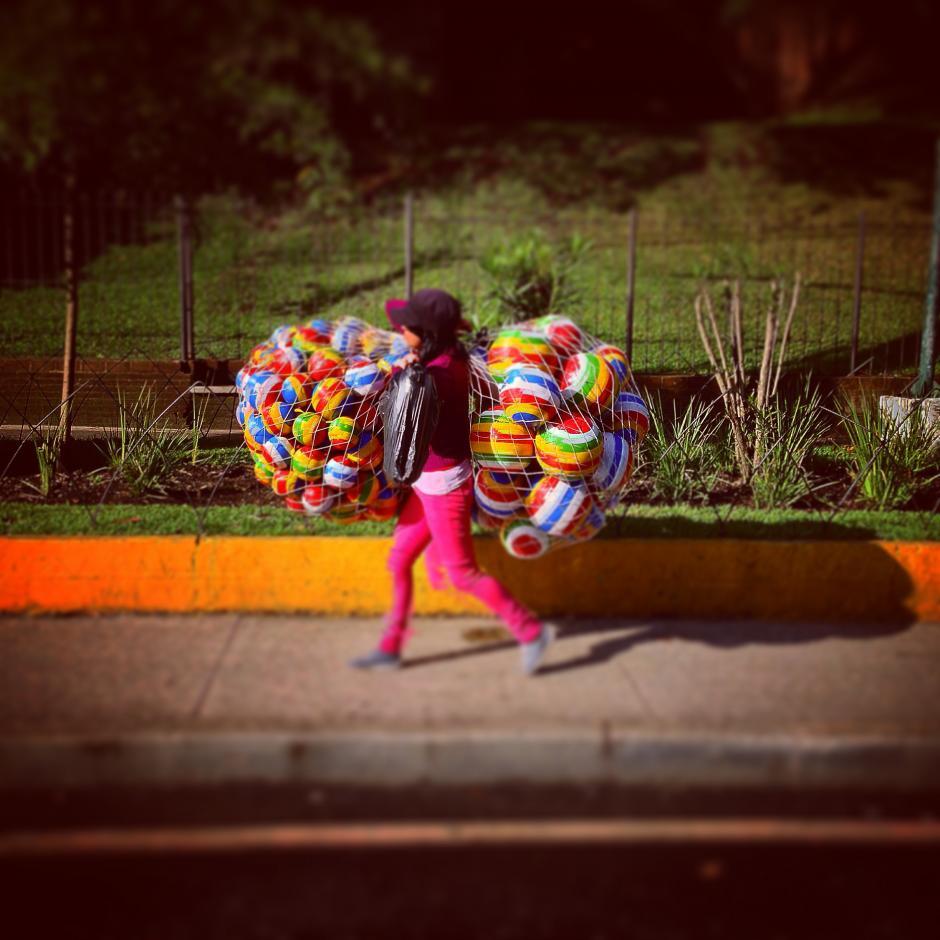 """Las coloridas pelotas de hule, más conocidas como de """"tripa de coche"""", son esos juguetes de infancia con la que muchos jugaron. Esta jovencita las vende en el Obelisco. (Foto: Jesús Alfonso/Soy502)"""
