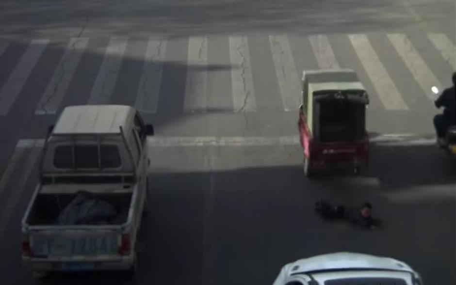 El niño cae en plena carretera. (Captura de pantalla: YouTube/RT)