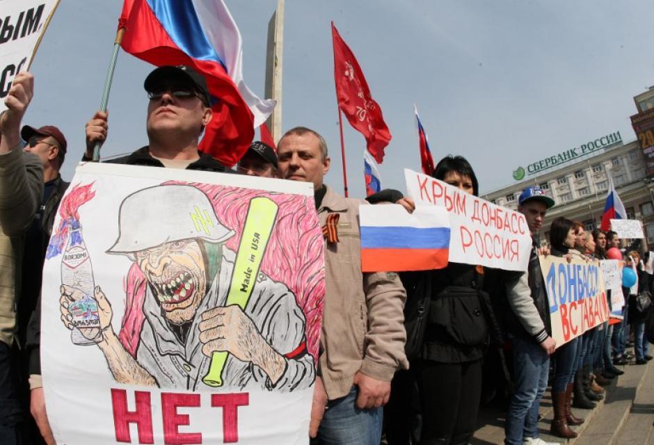 """Un activista pro-ruso sostiene un signo con el texto """"fascista ucraniano"""" durante una manifestación en el centro de la ciudad ucraniana oriental de Donetsk el 15 de marzo de 2014 (Foto: AFP/ Alexander Khudoteply"""