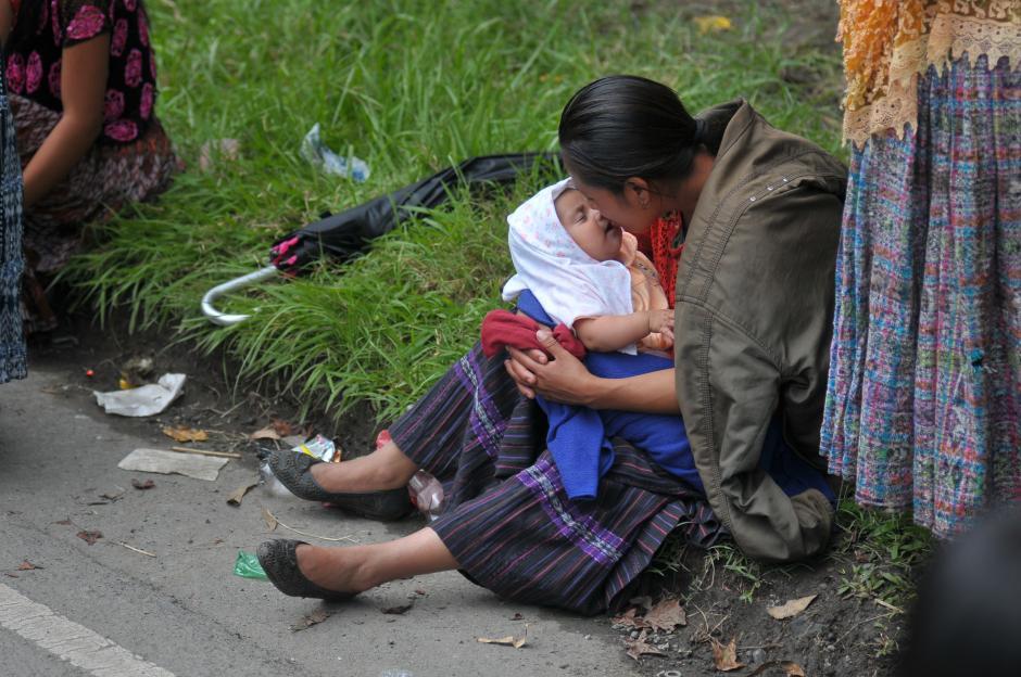 Una madre que participa en el bloqueo besa a su hijo en medio de la manifestación. (Foto: Byron de la Cruz/Soy502)