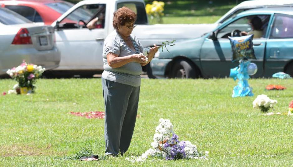 Una mujer coloca flores en un cementerio previo a que se celebre el Día de Todos los Santos.(Foto:Juan Carlos Raxón/Nuestro Diario)