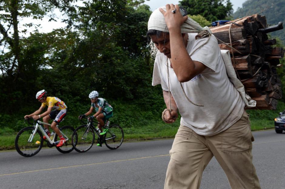 Mientras la caravana de ciclistas pasaba por la carretera este trabajador transporta leña sobre su espalda.(Foto: Diego Galiano/Nuestro Diario)