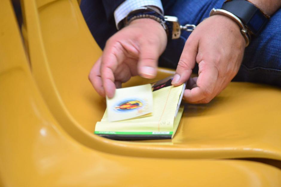 Un pequeño libro de rezos tiene en sus manos Gustavo Alejos, acusado en el caso de Cooptación del Estado. (Foto: Jesús Alfonso/Soy502)