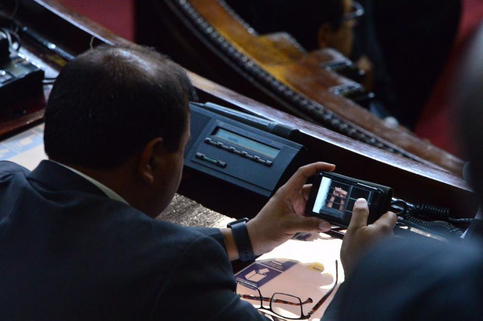 El diputado representante de Huehuetenango, Mike Mérida, mira videos en su curul. (Foto: Jesús Alfonso/Soy502)