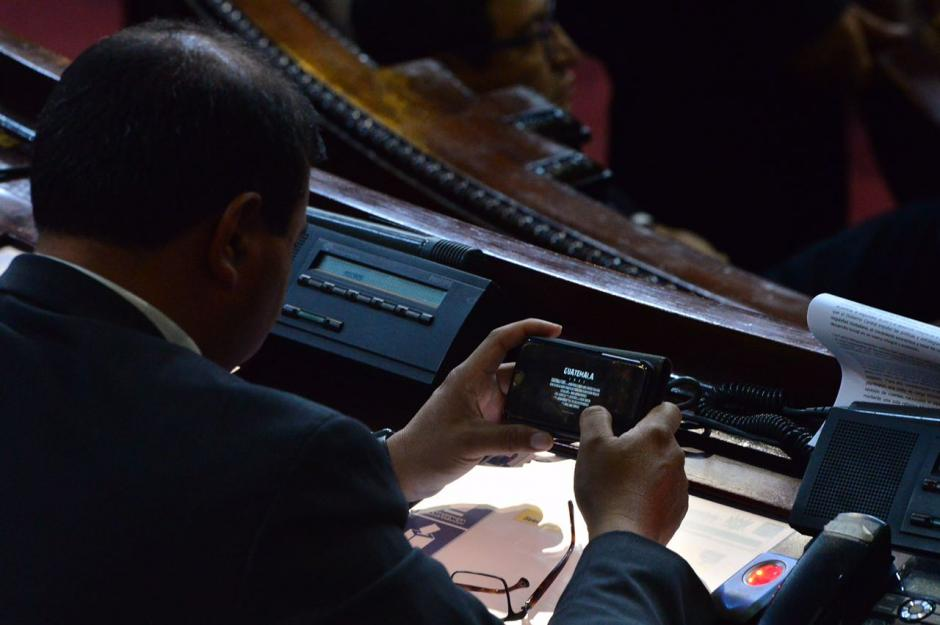 Mike Mérida pertenece a la Bancada MR y optó por entretenerse de esta forma mientras otros diputados discutían en la sesión. (Foto: Jesús Alfonso/Soy502)