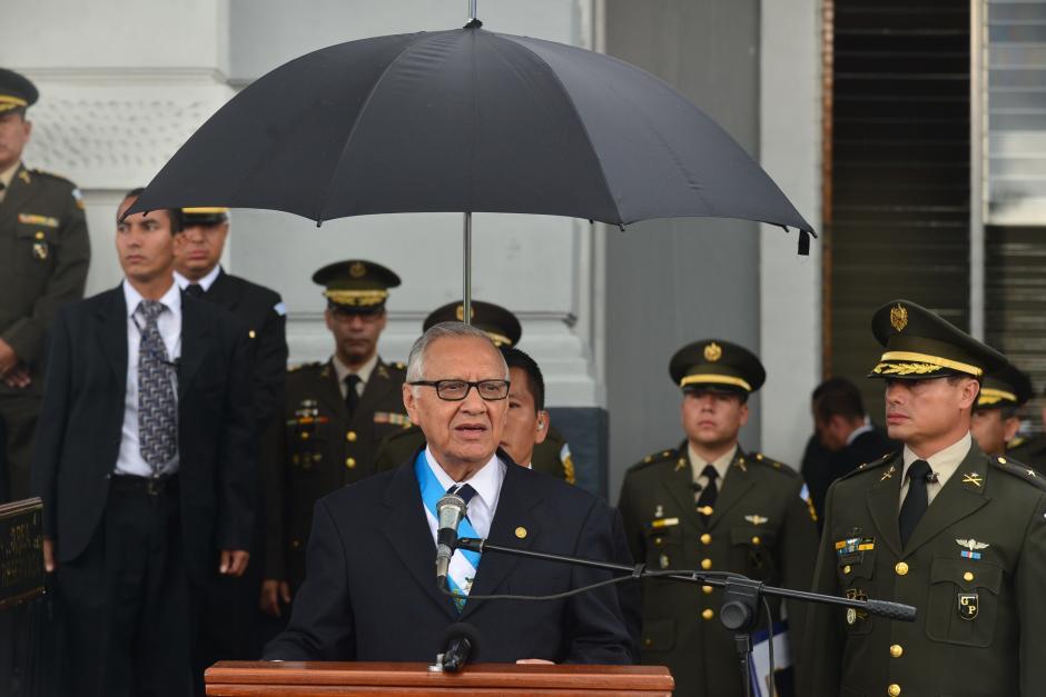 Un agente de SAAS sostiene un paraguas sobre el presidente Alejandro Maldonado, durante discurso a el Ejército de Guatemala. (Foto: Wilder López/Soy502)