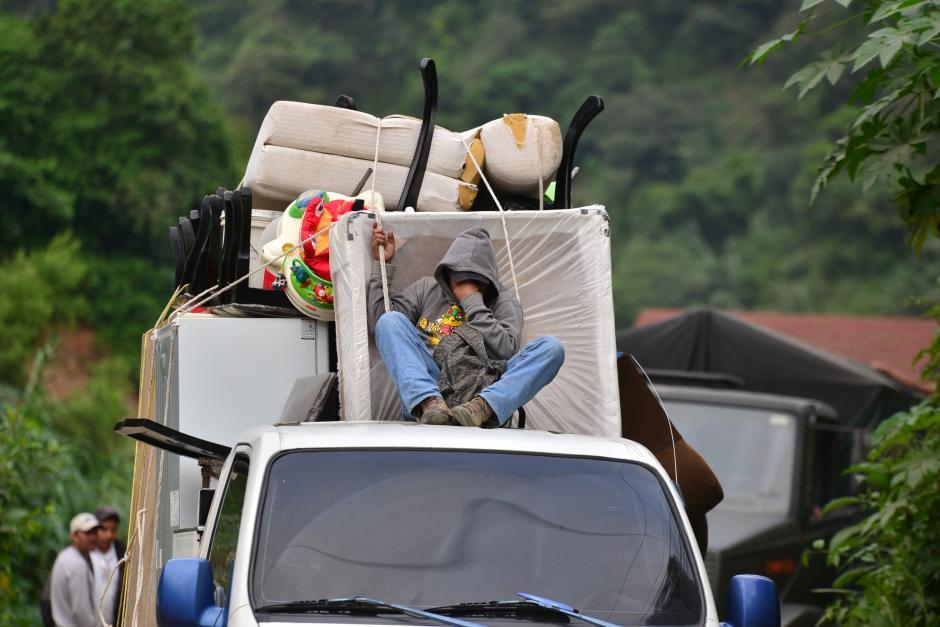 Un joven cubre su rostro al momento de salir del que hasta hace una semana era su hogar, con las pocas pertenencias que pudo sacar de El Cambray II. (Foto: Wilder López/Soy502)