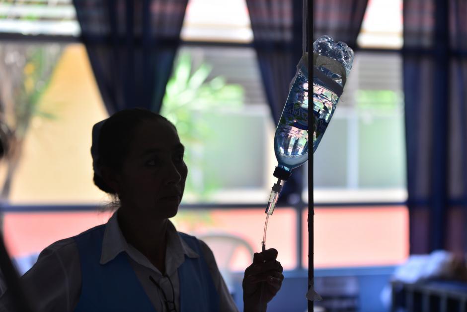 Una enfermera coloca una solución líquida utilizando una botella de plástico ya que no cuentan con los implementos necesarios. (Foto: Wilder López/Soy502)