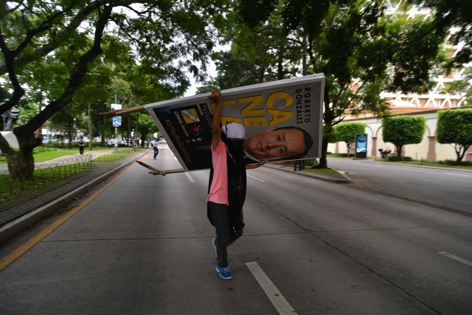 Activistas de la USAC comenzaron a retirar la propaganda política de la Avenida La Reforma. (Foto: Wilder López/Soy502)