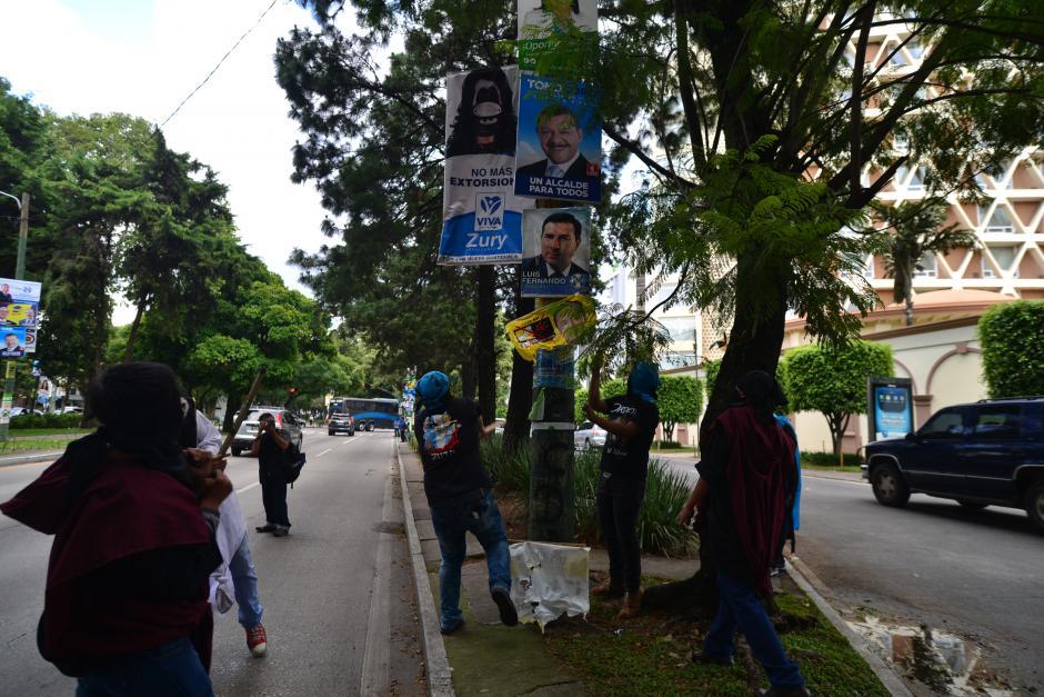 Varios activistas golpean la propaganda para intentar tirarla.(Foto: Wilder López/Soy502)