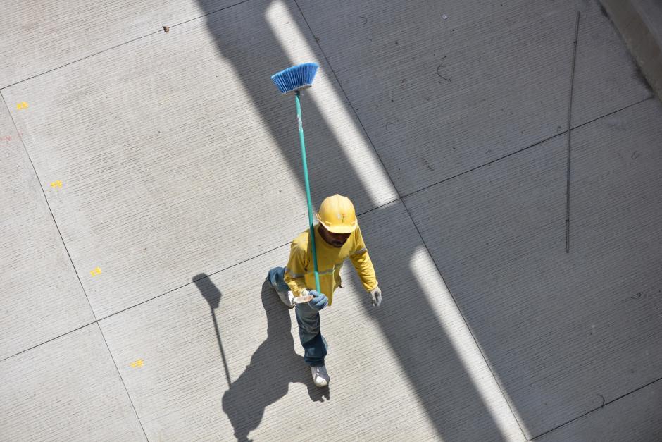 Un obrero barre la pista para pintar las líneas que dividen los dos carriles que la conforman. (Foto: Wilder López/Soy502)