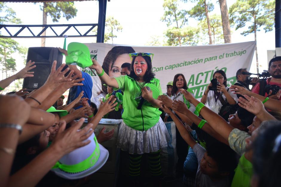 La animadora del evento, una payasita arroja una gorra entre los simpatizantes de la UNE. (Foto: Wilder López/Soy502)