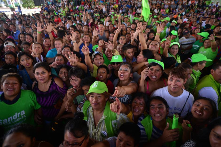 Mujeres se acercan a la tarima levantando las manos para poder participar en las dinámicas y ganar premios. (Foto: Wilder López/Soy502)