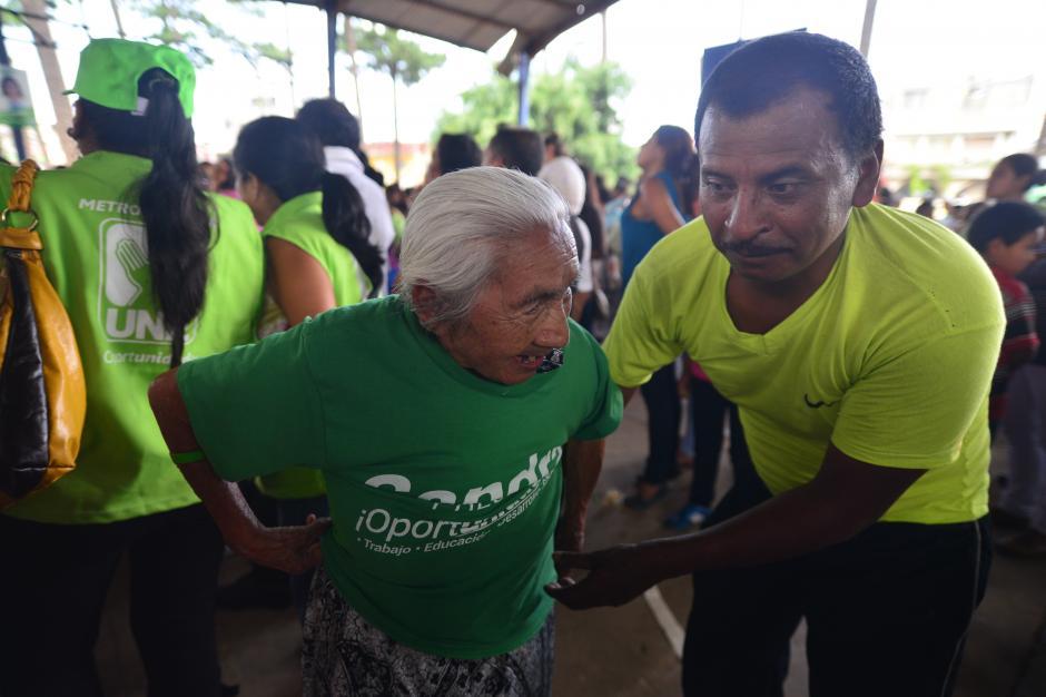Una anciana recibe ayuda para colocarse una playera que le regalaron en el mitin de la UNE. (Foto: Wilder López/Soy502)