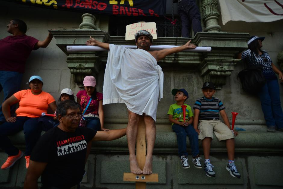 Un personaje inusual en la marcha, simuló ser crucificado pidiendo la renuncia de los mandatarios. (Foto: Wilder López/Soy502)