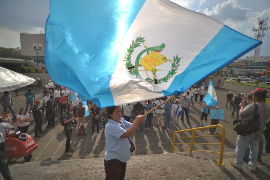 Una mujer ondea una bandera durante la entonación del Himno Nacional. (Foto: Wilder López/Soy502)
