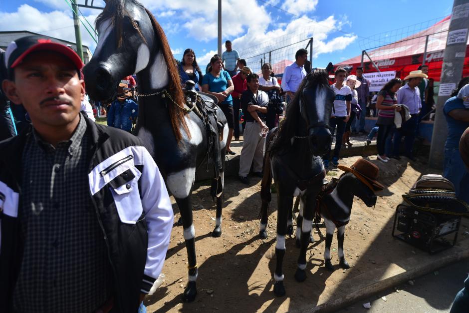 Vecinos de Mixco se tomaron un momento del día para observar el desfile. (Foto: Wilder López/Soy502)