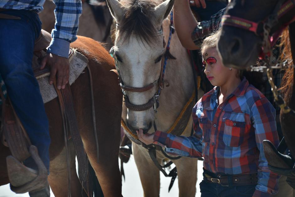Una niña es rodeada por jinetes, cuando jugaba con uno de los ejemplares que desfilaron. (Foto: Wilder López/Soy502)