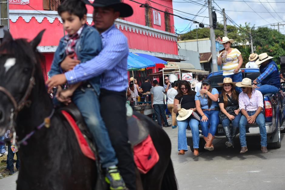 Un grupo de personas toma un descanso del desfile y observan la actividad desde la palangana de un pickup. (Foto: Wilder López/Soy502)