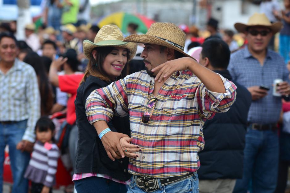 Una pareja baila al ritmo de música norteña, la cual acompañaba el desfile. (Foto: Wilder López/Soy502)