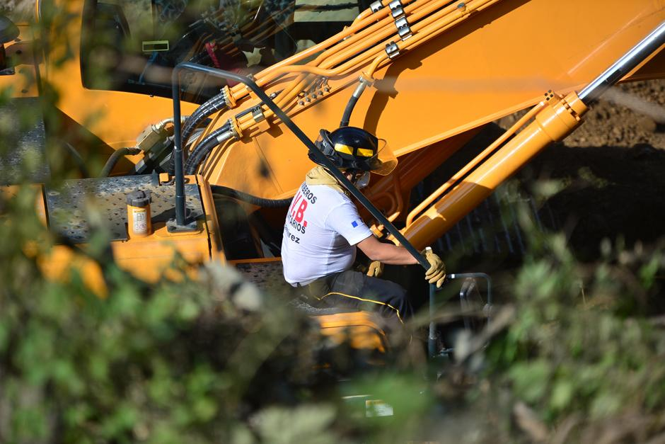 Un bombero Voluntario acompaña al operario de esta retroexcavadora con el fin de alertarle si el aparato se encuentra con algún cuerpo de los desaparecidos. (Foto: Alejandro Balan/Soy502)