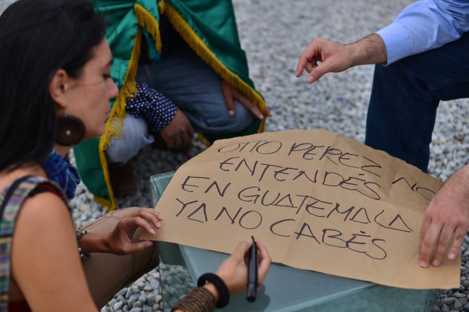 Una manifestante elabora un cartel dirigido al presidente Otto Pérez Molina pidiéndole la renuncia del cargo. (Foto: Wilder López/Soy502)