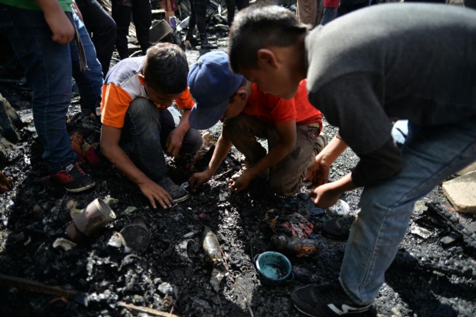 Varios niños buscan rescatar sus pertenencias de lo que dejó el incendio. (Foto: Wilder López/Soy502)