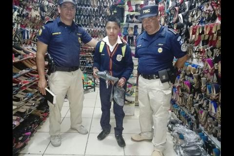 Agentes de policía le compran zapatos a un niño en Chichicastenango
