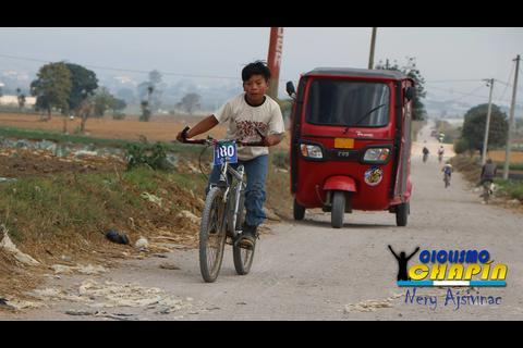 Niño apasionado por el ciclismo compite con botas de hule